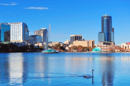 florida: Orlando Lake Eola in the morning with urban skyscrapers and clear blue sky with swan.