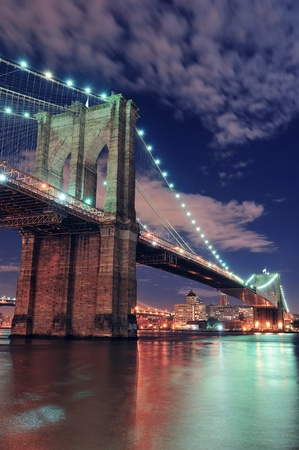 brooklyn bridge: Brooklyn Bridge closeup over East River at night in New York City Manhattan with lights and reflections. Stock Photo