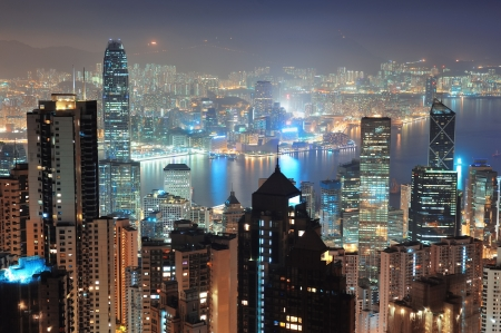 Hong Kong city skyline at night with Victoria Harbor and skyscrapers illuminated by lights over water viewed from mountain top. photo