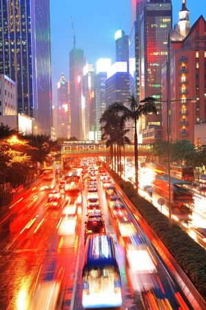 Hong Kong street with busy traffic and skyscraper office at dusk. photo