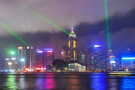 laser show: Hong Kong skyline at night with light beams over sea with reflections.