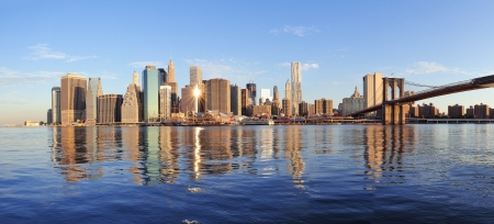 Brooklyn Bridge with lower Manhattan skyline panorama in the morning with cloud and river reflection over East River in New York City photo