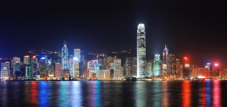 kong: Hong Kong city skyline at night over Victoria Harbor with clear sky and urban skyscrapers.