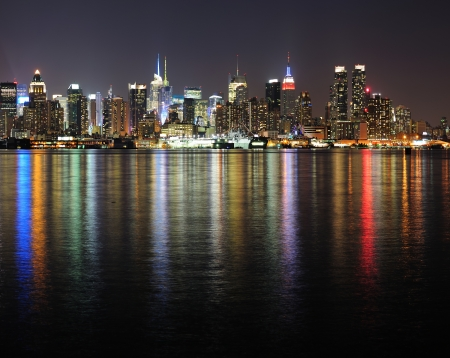 empire state building: New York City Manhattan midtown skyline panorama at night with lights reflection over Hudson River.