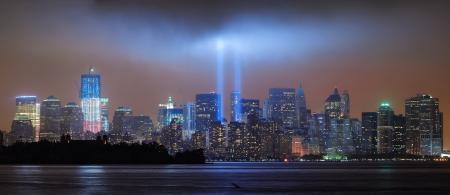 szeptember: New York City Manhattan belvárosi városkép éjszaka Liberty Park fénysugarakat emlékére szeptember 11-nézve New Jersey vízparton.