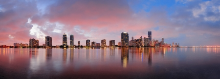 miami sunset: Miami city skyline panorama at dusk with urban skyscrapers over sea with reflection Stock Photo