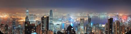 panorama city panorama: Hong Kong horizonte de la ciudad panorama de la noche con el puerto de Victoria y los rascacielos iluminados por las luces sobre el agua visto desde la parte superior de la monta�a. Foto de archivo
