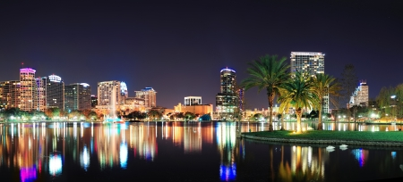 orlando: Orlando downtown skyline panorama over Lake Eola at night with urban skyscrapers and clear sky.