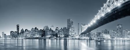 クイーンズボロ橋川反射とミッドタウン マンハッタンのスカイラインとの夜にニューヨークのイーストリバー黒と白に点灯します。