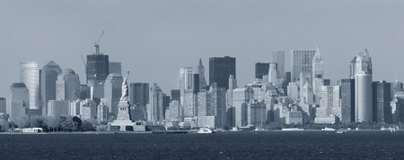 New York City lower Manhattan skyline black and white with Statue of Liberty and urban city skyline over river panorama view. photo