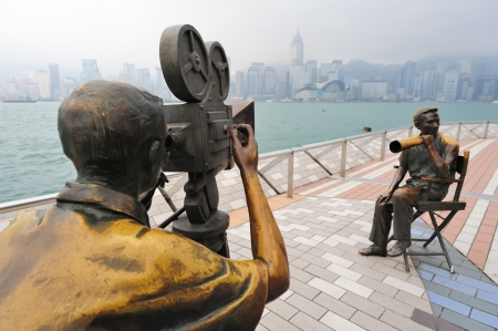 famous industries: HONG KONG, CHINA - APR 17: Statue and skyline in Avenue of Stars on April 17, 2012 in Hong Kong, China. The promenade honours celebrities of the Hong Kong film industry as the famous city attraction.