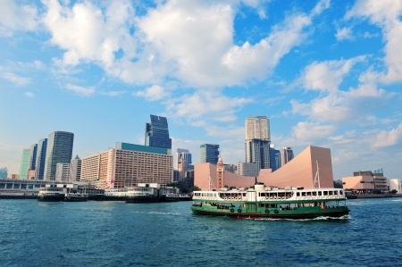 Urban architecture in Hong Kong Victoria Harbor in the day with blue sky, boat and cloud. photo