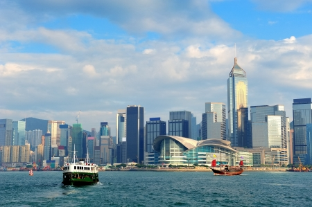 victoria: Urban architecture in Hong Kong Victoria Harbor in the day with blue sky, boat and cloud. Stock Photo