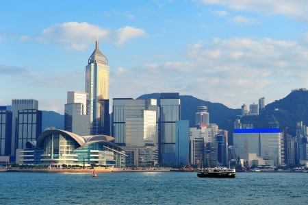Urban architecture in Hong Kong Victoria Harbor in the day with blue sky, boat and cloud. Stock Photo