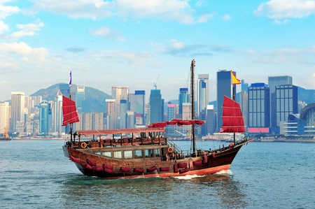 Boat in Victoria Harbor in Hong Kong with city skyline in the day photo