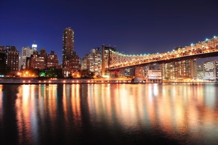 new york notte: Queensboro Bridge over New York East River fiume al tramonto, con riflessioni e midtown skyline di Manhattan illuminato.