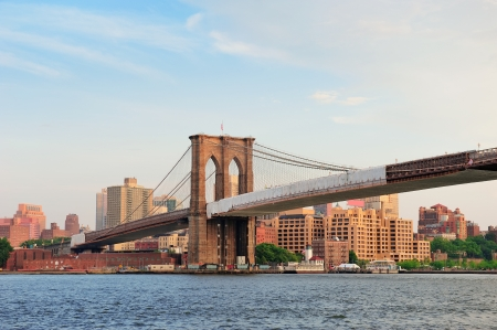 Brooklyn Bridge over East River viewed from New York City Lower Manhattan waterfront at sunset. photo
