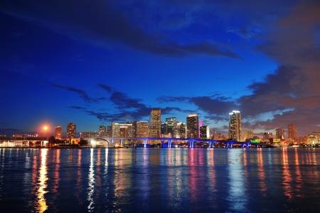 都市の高層ビルや反射と海に架かる橋の夕暮れ時にマイアミ都市スカイラインのパノラマ