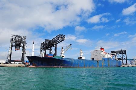 Cargo ship at Miami harbor with crane and blue sky over sea. photo