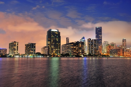 city of miami: Miami city skyline panorama at dusk with urban skyscrapers over sea with reflection Stock Photo