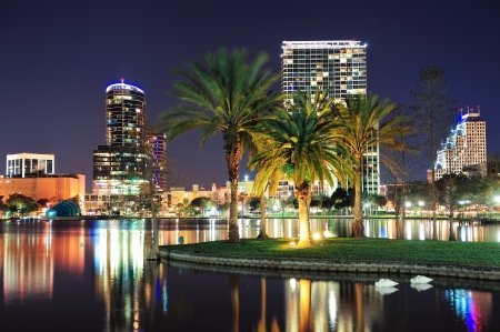 florida landscape: Orlando downtown skyline panorama over Lake Eola at night with urban skyscrapers, tropic palm tree and clear sky.