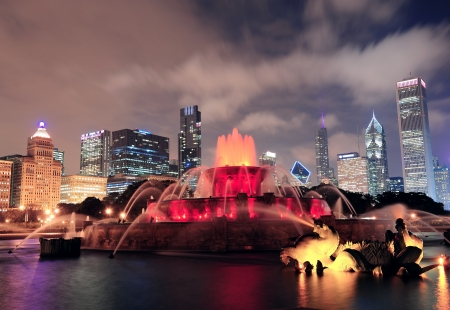 Chicago skyline with skyscrapers and Buckingham fountain in Grant Park at night lit by colorful lights. photo