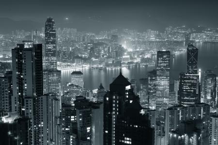 городской пейзаж: Гонконг город небоскребов в ночное время с гавань Виктория и небоскребы освещенный огнями над водой смотреть с вершины горы в черном и белом. Фото со стока