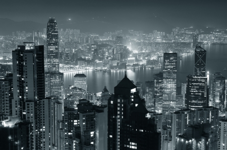 Hong Kong city skyline at night with Victoria Harbor and skyscrapers illuminated by lights over water viewed from mountain top in black and white. Stock Photo