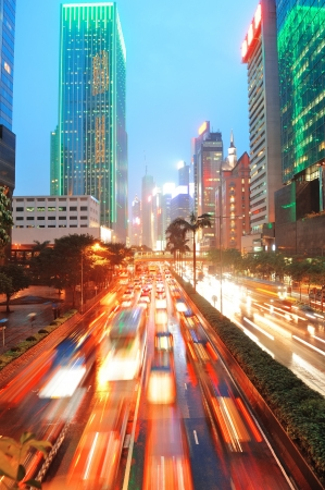 Hong Kong street with busy traffic and skyscraper office at dusk. Stock Photo