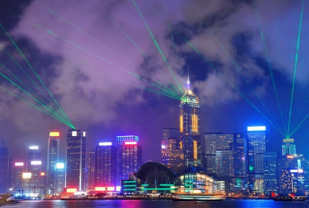 Hong Kong skyline at night with light beams over sea with reflections