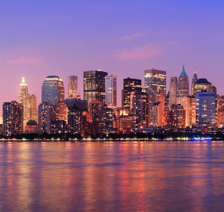 New York City Manhattan downtown skyline bij zonsondergang met wolkenkrabbers verlicht dan Hudson River panorama Stockfoto