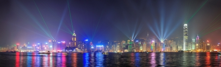 laser show: Hong Kong skyline at night with lights and skyscrapers over sea with laser beams