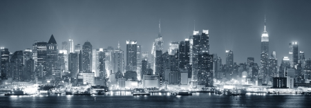 New York City Manhattan midtown skyline black and white at night with skyscrapers lit over Hudson River with reflections   Stock Photo - 14361176