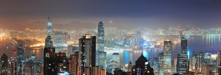 Hong Kong city skyline panorama at night with Victoria Harbor and skyscrapers illuminated by lights over water viewed from mountain top
