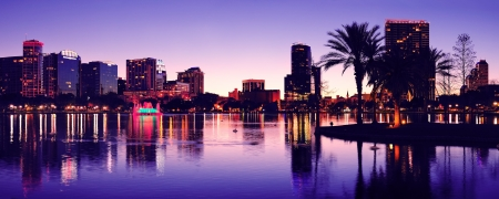 lake district: Orlando downtown skyline panorama silhouette over Lake Eola at dusk with urban skyscrapers