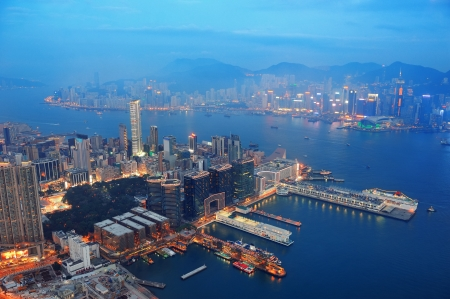 port: Victoria Harbor aerial view with Hong Kong skyline and urban skyscrapers at night.