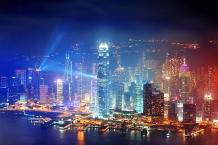 hong kong: Victoria Harbor aerial view with Hong Kong skyline and urban skyscrapers at night.