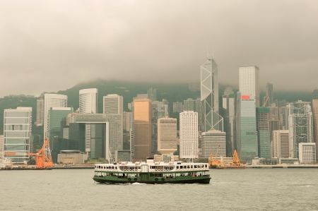 Hong Kong skyline with boats in Victoria Harbor in yellow tone.  photo