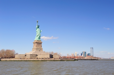 statue of liberty: Statue of Liberty on Liberty Island and New York City Manhattan downtown skyline with skyscrapers and blue sky Stock Photo