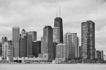hancock building: Chicago city urban skyline black and white with skyscrapers over Lake Michigan with cloudy blue sky.