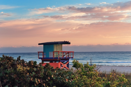 miami south beach: Miami South Beach sunrise with lifeguard tower and coastline with colorful cloud and blue sky.
