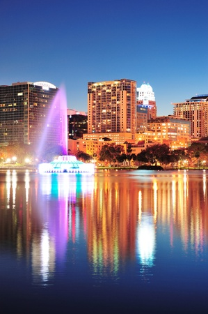 orlando: Orlando downtown skyline panorama over Lake Eola at night with urban skyscrapers, fountain and clear sky.