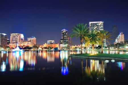 Orlando downtown skyline panorama over Lake Eola at night with urban skyscrapers, tropic palm tree and clear sky. photo