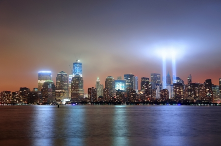 september 11: New York City Manhattan downtown skyline at night from Liberty Park with light beams in memory of September 11 viewed from New Jersey waterfront.