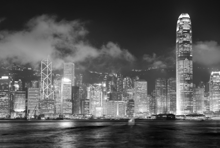 hong kong night: Hong Kong skyline at night with clouds over Victoria Harbour in black and white.