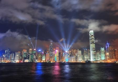 Hong Kong skyline 's nachts met lichtstralen over zee met reflecties.