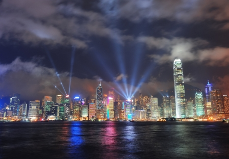 Hong Kong skyline at night with light beams over sea with reflections.