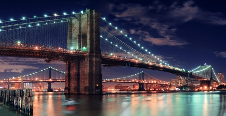 new buildings: Brooklyn Bridge over East River at night in New York City Manhattan with lights and reflections. Stock Photo