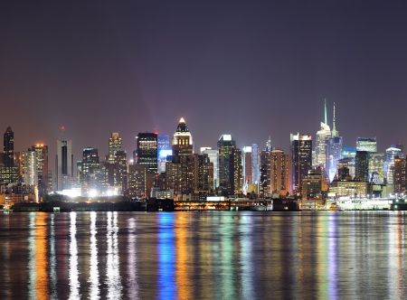 New York City Manhattan midtown skyline at night with lights reflection over Hudson River viewed from New Jersey Weehawken waterfront
