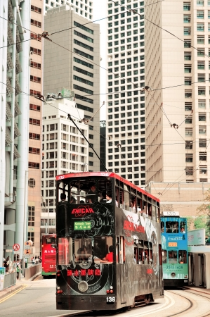 HONG KONG, CHINA - APR 23: Double-deck bus with skyscrapers on April 23, 2012 in Hong Kong, China. The Double-deck trams system in Hong Kong is one of three and the most famous in the world.
